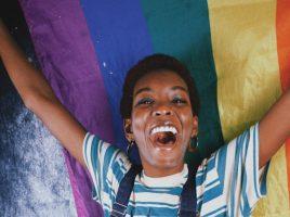 Eine farbige junge Frau, die eine Regenbogen-Fahne hinter sich hält