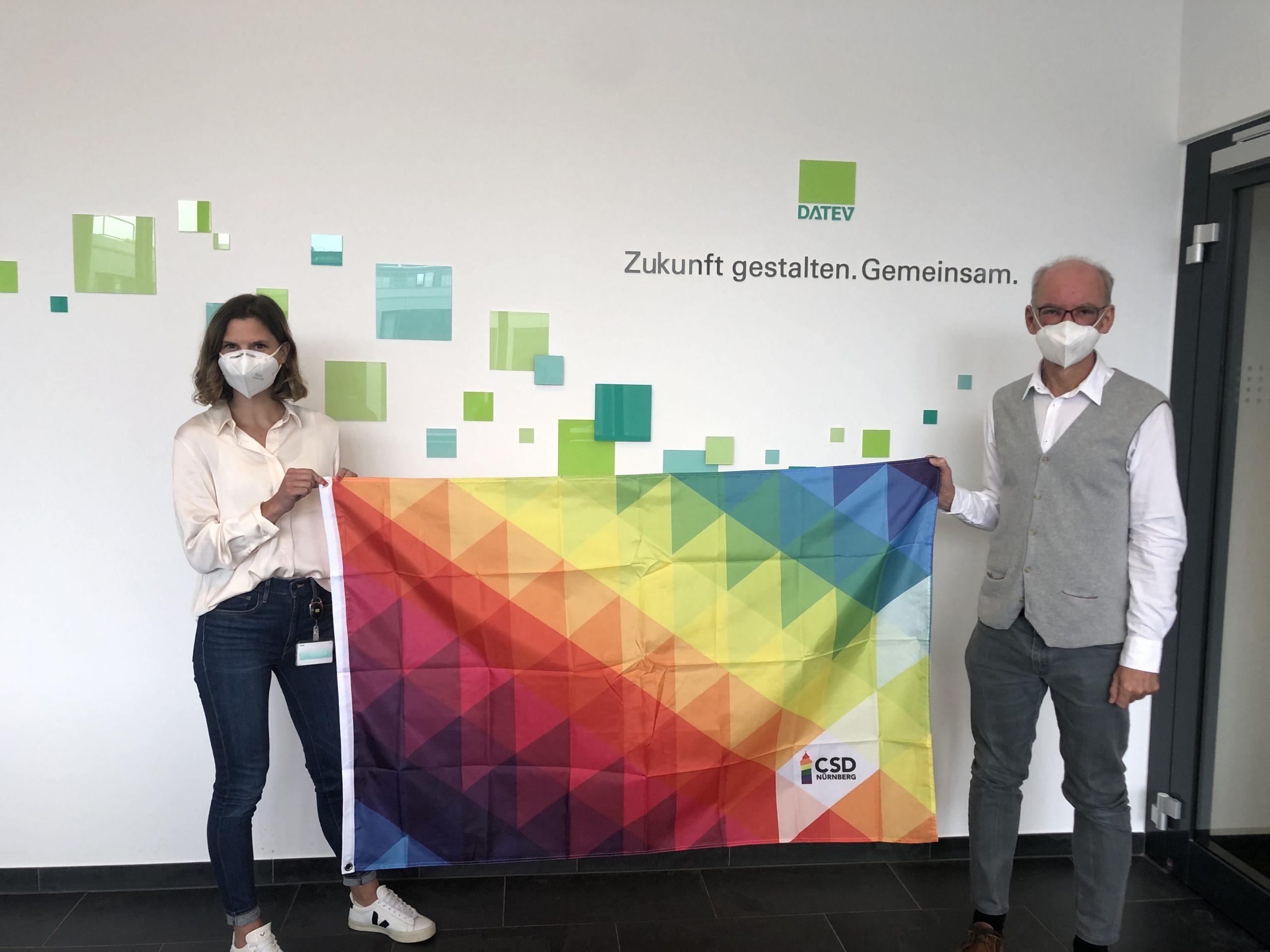 Roland Mair und eine Kollegin halten die Regenbogen-Flagge