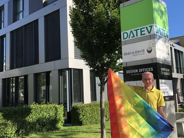 Roland Mair hält eine Regenbogenflagge vor dem DATEV-Gebäude