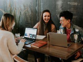 Drei junge Menschen sitzen am Tisch und arbeiten zusammen
