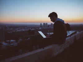 Ein junger Mann sitzt mit seinem Laptop auf einem Hochhausdach.
