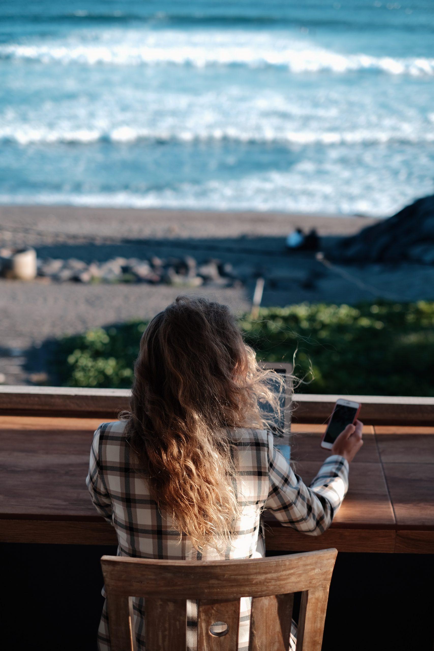Eine Frau arbeitet mit Blick auf einen Strand